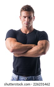 Confident Young Muscled Man in Black Shirt Crossing Arms in Front of the Camera with Serious Face. Isolated on White Background.