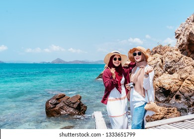 confident young muslim friend of travellers on the beach. Travel concept. Tourist friend looking for take photo with sea background. two beautiful asian woman.