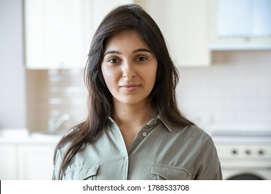 Confident young pretty indian ethnicity woman looking at camera alone at home in kitchen. Happy beautiful millennial hindu lady housewife in India indoors, close up face front headshot portrait.