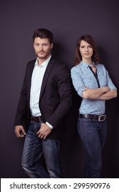 Confident Young Professional Couple in Semi-Formal Outfit Leaning Against Dark Gray Wall Background and Staring at the Camera.