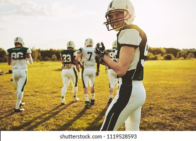 Confident young quarterback walking on a field on a sunny afternoon with a group of young American football players during a practice game