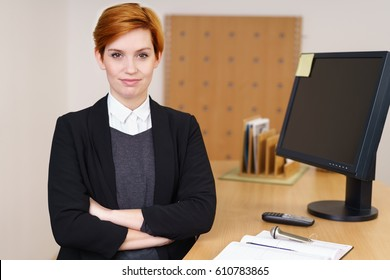 Confident young receptionist behind the front desk in a corporate enterprise or hotel standing with folded arms looking at the camera with a quiet thoughtful smile