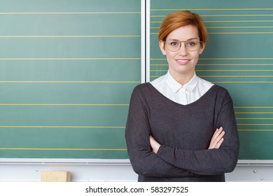 Confident young redhead woman with a friendly smile standing with folded arms against a green blackboard