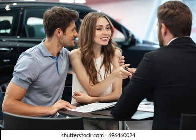 Confident young salesman explaining all the new car features to the young attractive owners