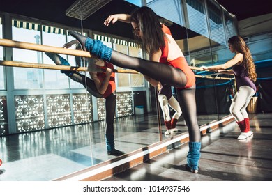 Confident young sportive women in bodysuits practicing in ballet studio stretching with barre.