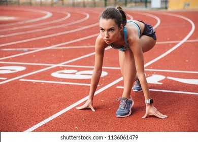 Confident young sportswoman getting ready to run a distance at the stadium