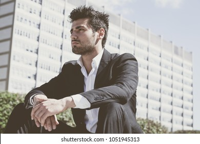 Confident young successful man sitting in the city. Behind him a modern office building. Trendy hair, white shirt and jacket.