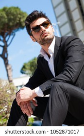 Confident young successful man sitting in the city. Wearing sunglasses, behind him a modern office building. Trendy hair, white shirt and jacket.