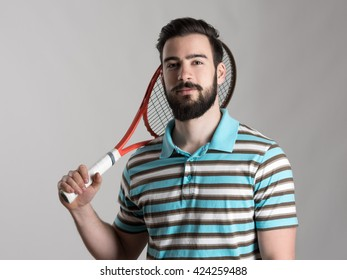 Confident young tennis player in polo shirt holding racket on the shoulder