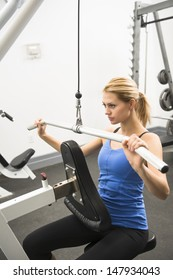 Confident young woman doing weight exercise in health club