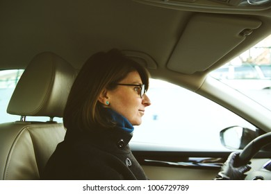 Confident young woman driving in luxury car with leather interior