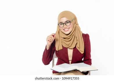 Confident young woman with hijab sitting and holding book on white background.