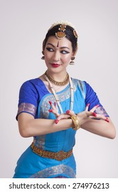 Confident young woman performing classical dance on gray background