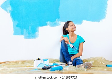 confident young woman portrait while painting new apartment renovating with blue color paint