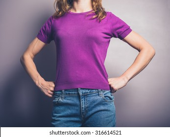 A confident young woman in purple shirt is standing in a powerful pose with her hands on her hips