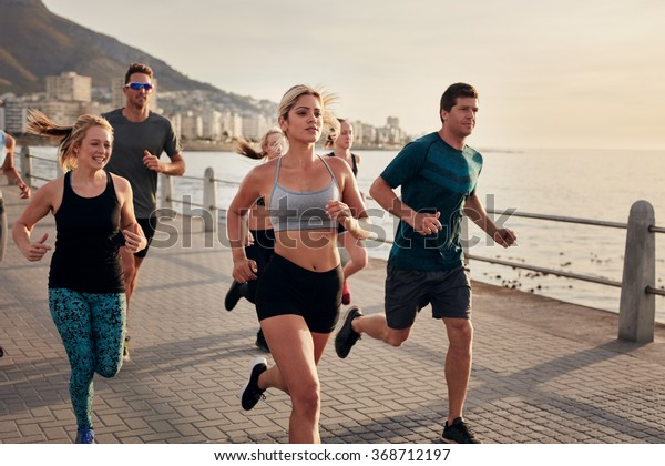 Confident young woman runs with friends. Group of young people doing running workout together in morning.