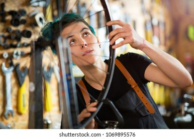 Confident young woman working in a bicycle repair shop