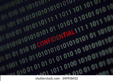 'Confidential' word in the middle of the computer screen surrounded by numbers zero and one. Image is taken in a small angle.