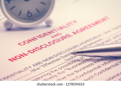 Confidentiality and non-disclosure agreement form and a pen, business legal document concept. Confidentiality agreement is legal contract between two parties that outlines confidential issues together