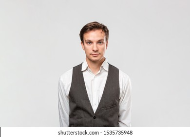 Confindent handsome man in a white shirt and grey vest looking at the camera standing isolated over grey background.