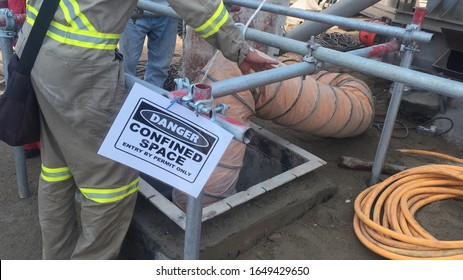 Confined Space Entry job with person observing entrant inside the silo through the manhole. Ventilation through ducting and warning signage at site