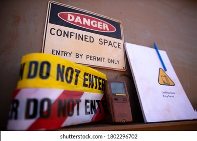 Confined space warning sign permit entry by permit only and red barricade danger tape, yellow caution tape gas test leak atmosphere with defocused confined space permit book template, pen  background