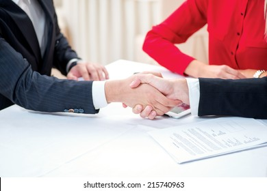 Confirmation of sponsorship. Three successful and confident businesspeople shake hands. Businesspeople in formal attire sitting in an office at a desk close-up view of hands