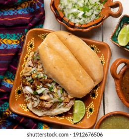 Confit pork sandwich called Torta de carnitas on white background. Traditional Mexican food