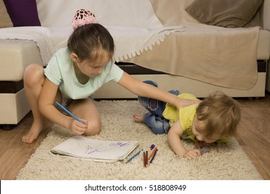 The conflict between a boy and a girl. Older sister younger brother offends. Sister takes his brother's pen. Children quarrel over the drawing. Children with paint. siblings Psychology.