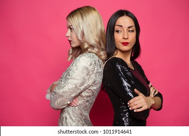 Conflict between friends. Two angry and resentful girlfriend standing back to back on a pink background.