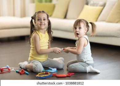Conflict between little sisters playing at home. Kids are fighting, toddler girl takes toy, sibling relationships