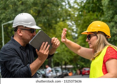 Conflict and disagreement at work on construction site. Angry construction boss yelling at an architect threatening to hit her with a digital tablet