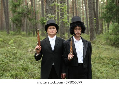 Conflict, duel, two men with pistols in forest, victorian clothes