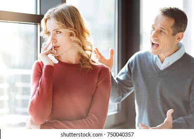 Conflict in the family. Angry emotional man standing behind his wife and shouting at her while expressing his emotions