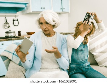 Conflict Of Generations Grandmother With Her Granddaughter Cannot Understand Each Other's Gadgets Granny Holding Mobile Or Smart Phone Making Photos