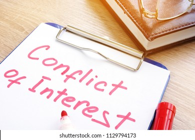 Conflict of interest written on a piece of paper.