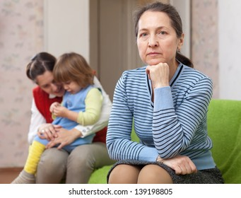 The conflict of intergenerational. Sad woman against daughter with baby at home