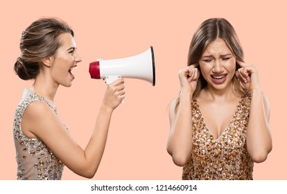 Conflict. One woman shouts into a megaphone at another woman. Pink background.