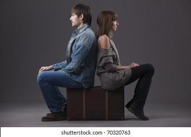conflict in relationship - man and woman sitting on suitcase back on back