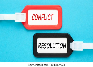 Conflict and resolution written on luggage tags on blue background. Business concept. Top view.