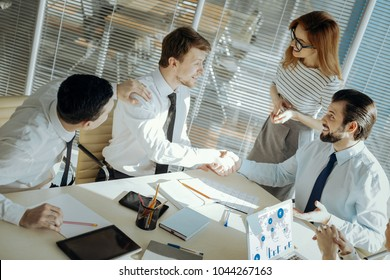 Conflict solved. Pleasant male office workers shaking hands, having reconciled with each other with the help of their colleagues and a team leader