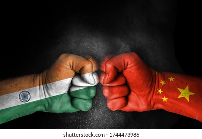 Conflict and tension between India and China, male fists with flags painted on skin isolated on black background - fight and conflict between two countries concept