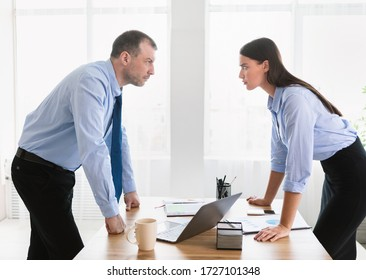 Conflict At Work. Businessman And Businesswoman Staring At Each Other Arguing Having Confrontation Standing In Modern Office.