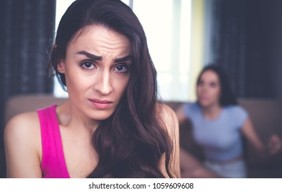 Conflicts between friends. In the foreground an offended and frustrated young woman looks into the camera, and against the background her friend yells at her.