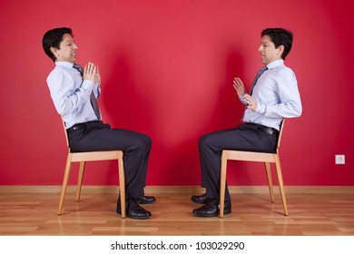 Confrontation between two twin businessman sited next to a red wall
