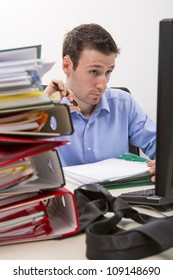 Confused accountant looking at work surrounded by huge piles of documents.