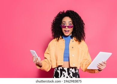 confused african american woman in sunglasses holding smartphone and digital tablet on pink