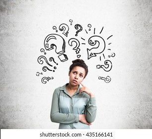 Confused african american woman trying to find answers to her questions with question mark sketches on concrete background
