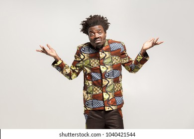 Confused afro man puzzled and say don't know, maybe. Indoor, isolated on gray background