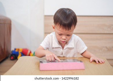 Confused aggressive Asian 2 - 3 years old toddler boy using tablet pc playing game, watching a video from tablet pc. Kids playing with tablet computer, Gadget-addicted children, pseudo-autism concept